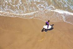 Το Surfer που περπατά κατά μήκος της θάλασσας πυροβολήθηκε από την κορυφή στοκ φωτογραφία