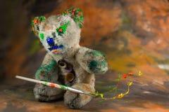 Το Teddy αντέχει κάθεται και κάνει μαγικός με το χρώμα στοκ εικόνες