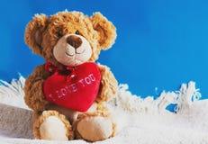 Το Teddy αντέχει και μεγάλη κόκκινη καρδιά με το κείμενο που απομονώνεται σ' αγαπώ Στοκ Εικόνες