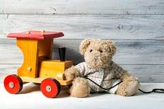 Το Teddy αντέχει και παίζει ξύλινο τραίνο, ξύλινο υπόβαθρο Στοκ Εικόνα