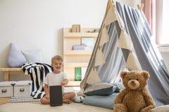 Το Teddy αντέχει και σκηνή σε ένα εσωτερικό χώρων για παιχνίδη όπου ένα νέο αγόρι παίζει στοκ εικόνες