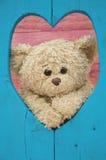 Το Teddy αντέχει μέσω της ξύλινης καρδιάς αγάπης Στοκ Φωτογραφία