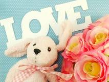 Το Teddy αντέχει με τη λέξη αγάπης και τα τεχνητά τριαντάφυλλα ανθίζουν με το ρόδινο υπόβαθρο Στοκ Εικόνα