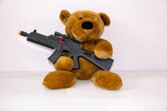 Το Teddy αντέχει με το πυροβόλο όπλο παιχνιδιών η έννοια του πολέμου, ασφάλεια παιδιών, τρομοκρατία, για να προστατεύσει τα παιδι στοκ εικόνα