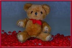 Το Teddy αντέχει σε μια κόκκινη συνεδρίαση πλαισίων που περιβάλλεται από τις κόκκινες καρδιές καραμελών για την ημέρα βαλεντίνων  Στοκ Φωτογραφία
