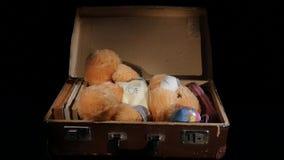 Το Teddy αντέχει σε μια παλαιά βαλίτσα δέρματος περιστρέφεται στο μαύρο υπόβαθρο απόθεμα βίντεο