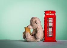 Το Teddy αντέχει στο κόκκινο τηλεφωνικό κιβώτιο στοκ φωτογραφία