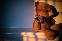 Το Teddy αντέχει τη συνεδρίαση κουκλών εκτός από το παράθυρο με το φως ηλιοβασιλέματος σπόλα Στοκ φωτογραφία με δικαίωμα ελεύθερης χρήσης