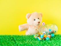 Το Teddy αντέχει το παιχνίδι εξετάζει μια κόκκινη καραμέλα μορφής καρδιών στο βάζο γυαλιού Στοκ Φωτογραφία