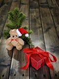 Το Teddy αντέχουν και το κιβώτιο Χριστουγέννων στο ξύλινο υπόβαθρο Στοκ Εικόνα