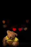 Το Teddy αφορά με την καρδιά bokeh το μαύρο υπόβαθρο Στοκ Φωτογραφίες