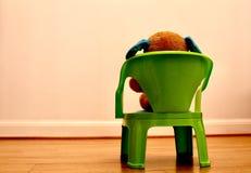 Το Teddy αφορά μια καρέκλα εξετάζοντας τον κενό άσπρο τοίχο στοκ φωτογραφία με δικαίωμα ελεύθερης χρήσης