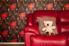 Το Teddy αφορά το μαλακό παιχνίδι τον κόκκινο καναπέ μοντέρνο Lifetsyle δέρματος στοκ φωτογραφία