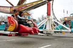 Το Teens απολαμβάνει το γρήγορα κινούμενο γύρο καρναβαλιού στην έκθεση Στοκ Φωτογραφία