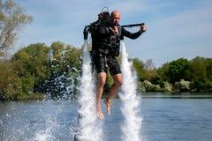 Το Thrillseeker, αθλητικός εραστής νερού, αθλητής που δένεται στο αεριωθούμενο LEV, μετεωρισμός αιωρείται πέρα από τη λίμνη με το Στοκ εικόνες με δικαίωμα ελεύθερης χρήσης