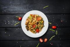 Το Udon ανακατώνει τα νουντλς τηγανητών με τα θαλασσινά και τα λαχανικά σε ένα άσπρο πιάτο στο μαύρο ξύλινο υπόβαθρο Στοκ εικόνα με δικαίωμα ελεύθερης χρήσης