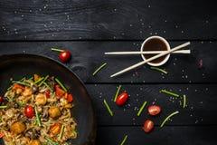 Το Udon ανακατώνει τα νουντλς τηγανητών με τα θαλασσινά και τα λαχανικά στο τηγάνι wok στο μαύρο ξύλινο υπόβαθρο Με chopsticks κα Στοκ Φωτογραφία