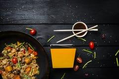 Το Udon ανακατώνει τα νουντλς τηγανητών με τα θαλασσινά και τα λαχανικά στο τηγάνι wok στο μαύρο ξύλινο υπόβαθρο Με ένα κιβώτιο γ Στοκ Φωτογραφίες