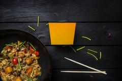 Το Udon ανακατώνει τα νουντλς τηγανητών με τα θαλασσινά και τα λαχανικά στο τηγάνι wok στο μαύρο ξύλινο υπόβαθρο Με ένα κιβώτιο γ Στοκ εικόνα με δικαίωμα ελεύθερης χρήσης