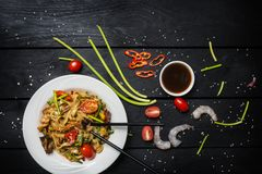 Το Udon ανακατώνει τα νουντλς τηγανητών με τα θαλασσινά σε ένα άσπρο πιάτο στο μαύρο υπόβαθρο Με chopsticks και τη σάλτσα Στοκ Εικόνα