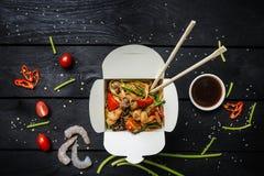 Το Udon ανακατώνει τα νουντλς τηγανητών με τα θαλασσινά σε ένα κιβώτιο στο μαύρο υπόβαθρο Με chopsticks και τη σάλτσα Στοκ Εικόνα