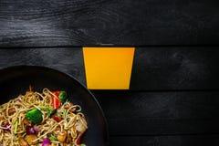 Το Udon ανακατώνει τα νουντλς τηγανητών με το κοτόπουλο και τα λαχανικά στο τηγάνι wok στο μαύρο ξύλινο υπόβαθρο Με ένα κιβώτιο γ Στοκ Φωτογραφίες