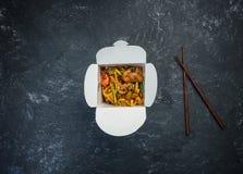 Το Udon ανακατώνει τα νουντλς τηγανητών με το κοτόπουλο σε ένα κιβώτιο σε ένα εκλεκτής ποιότητας χρωματισμένο υπόβαθρο Τοπ όψη Με Στοκ εικόνες με δικαίωμα ελεύθερης χρήσης