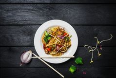 Το Udon ανακατώνει τα νουντλς τηγανητών με το κρέας ή το κοτόπουλο και τα λαχανικά σε ένα άσπρο πιάτο με chopsticks στοκ φωτογραφία με δικαίωμα ελεύθερης χρήσης