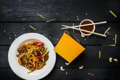 Το Udon ανακατώνει τα νουντλς τηγανητών με το κρέας και τα λαχανικά σε ένα άσπρο πιάτο στο μαύρο υπόβαθρο Με chopsticks και το κι Στοκ εικόνες με δικαίωμα ελεύθερης χρήσης