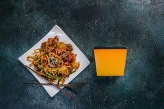 Το Udon ανακατώνει τα νουντλς τηγανητών με το κρέας και τα λαχανικά σε ένα τετραγωνικό άσπρο πιάτο Με chopsticks και το κιβώτιο γ Στοκ Εικόνα