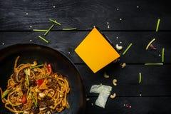 Το Udon ανακατώνει τα νουντλς τηγανητών με το κρέας και τα λαχανικά στο τηγάνι wok στο μαύρο ξύλινο υπόβαθρο Με ένα κιβώτιο για τ Στοκ Εικόνες