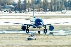 Το Unbranded μπλε αεροπλάνο που μετακινείται με ταξί μετά από με ακολουθεί αυτοκίνητο Στοκ φωτογραφίες με δικαίωμα ελεύθερης χρήσης