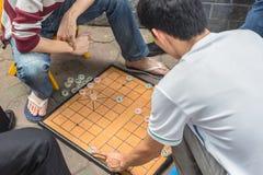 Το Unrecognizable άτομο παίζει το παραδοσιακό επιτραπέζιο παιχνίδι γνωστό ως κινεζικό σκάκι στοκ φωτογραφίες
