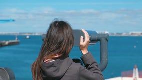 Το Unrecognizable brunette γυναικών εξετάζει μέσω των διοπτρών τη θάλασσα απόθεμα βίντεο