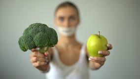 Το Vegan με το δεμένο με ταινία στόμα κρατά τα λαχανικά, έννοια της αυστηρής διατροφής, ζημιά στην υγεία απόθεμα βίντεο