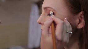 Το Visagiste κάνει makeup για το πρότυπο, επαγγελματικό makeup, απόθεμα βίντεο