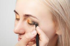 Το Visagiste με μια βούρτσα σε ένα χέρι που βάζει makeup στα μάτια του προτύπου, το άλλο χέρι τραβά το δέρμα του βλέφαρου με το χ στοκ φωτογραφία