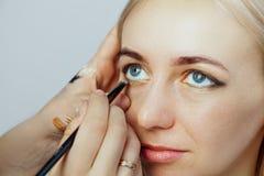 Το Visagiste με μια βούρτσα σε ένα χέρι που βάζει makeup στα μάτια του προτύπου, το άλλο χέρι τραβά το δέρμα του βλέφαρου με το χ στοκ εικόνες