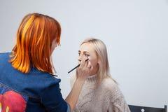 Το Visagiste με μια βούρτσα σε ένα χέρι που βάζει makeup στα μάτια του προτύπου, το άλλο χέρι τραβά το δέρμα του βλέφαρου με το χ στοκ φωτογραφία με δικαίωμα ελεύθερης χρήσης