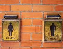 Το WC σημαδιών στο τούβλο εμποδίζει τον τοίχο, αναδρομικές μορφές στοκ φωτογραφίες