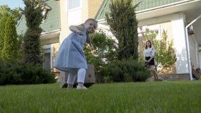 Τράβηγμα μικρών κοριτσιών cardbox με τα λουλούδια μέσω ενός πράσινου κήπου απόθεμα βίντεο