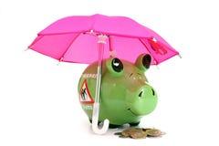Τράπεζα και νομίσματα Piggy κάτω από την έννοια ομπρελών του κεφαλαίου αποταμίευσης αποχώρησης στοκ φωτογραφίες