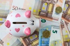 Τράπεζα Piggy και ευρο- τραπεζογραμμάτια σε έναν ξύλινο πίνακα Χρηματοδότηση αποταμίευση Στοκ Φωτογραφίες