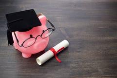Τράπεζα Piggy με ένα grad ΚΑΠ και δίπλωμα στον ξύλινο πίνακα, υποτροφία εκπαίδευσης στοκ φωτογραφίες