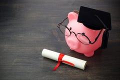 Τράπεζα Piggy με ένα grad ΚΑΠ και δίπλωμα στον ξύλινο πίνακα, υποτροφία εκπαίδευσης στοκ εικόνα