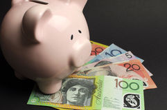 Τράπεζα Piggy με τα αυστραλιανά χρήματα σε ένα μαύρο κλίμα Στοκ Φωτογραφία
