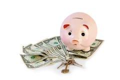 Τράπεζα Piggy με τα κλειδιά σπιτιών και χρήματα που απομονώνονται στο λευκό Στοκ Εικόνες