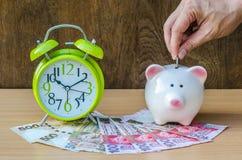 Τράπεζα Piggy με τα χρήματα και ξυπνητήρι στο ξύλινο επιτραπέζιο υπόβαθρο Στοκ Εικόνες