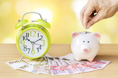 Τράπεζα Piggy με τα χρήματα και ξυπνητήρι στο ξύλινο επιτραπέζιο υπόβαθρο Στοκ φωτογραφία με δικαίωμα ελεύθερης χρήσης