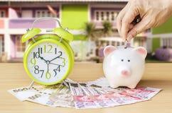 Τράπεζα Piggy με τα χρήματα και ξυπνητήρι στο ξύλινο επιτραπέζιο υπόβαθρο, Στοκ εικόνα με δικαίωμα ελεύθερης χρήσης